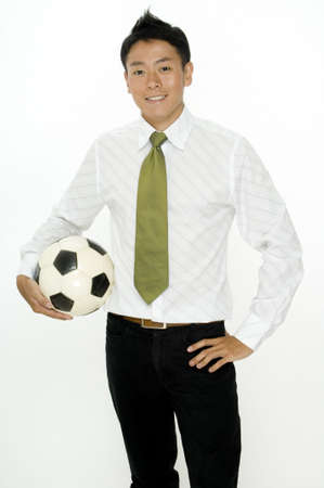A young businessman with a football under his arm photo