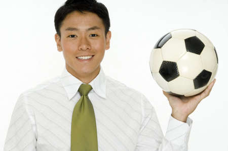 A young businessman holding a football (soccer ball) on white background photo