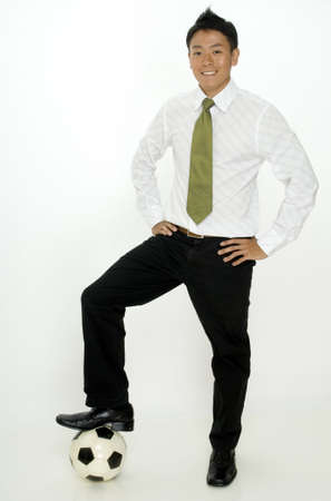 A young asian businessman with his foot on a football (soccer ball) photo