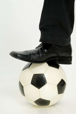 A leg and smart shoe stepping on a football (soccer ball) Stock Photo