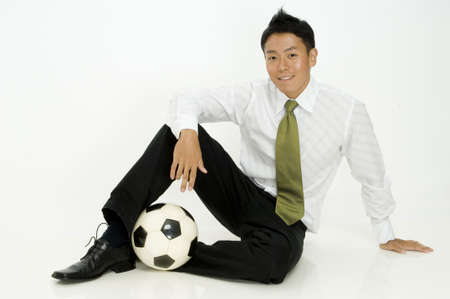 A young trendy businessman sitting with his ball photo