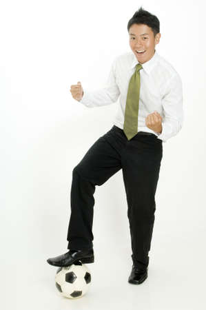 A young businessman celebrates as he steps on a ball