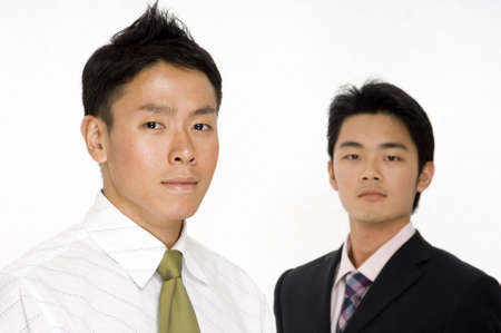 slightly: A young asian businessman (in focus) standing in front of a co-worker (slightly off focus) Stock Photo