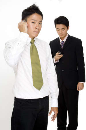 Two asian businessmen using their phones to communicate in different ways photo