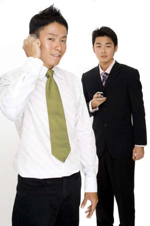 Two asian businessmen using mobile phones to communicate photo