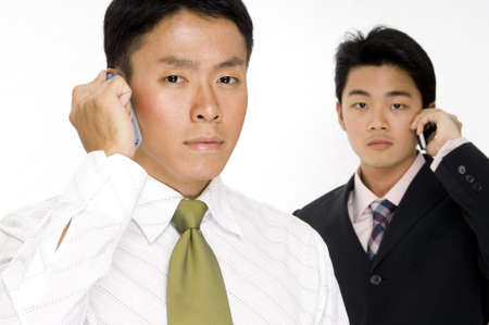 Two young asian businessmen using their phones photo