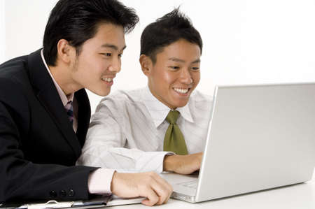 Two young asian businessmen working on a laptop computer photo