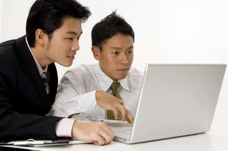 Two young asian men working on a laptop computer photo
