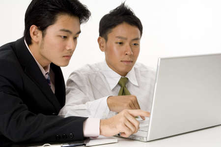 Two young businessmen working on a laptop computer photo