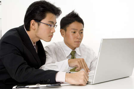 Two asian businessmen working on a laptop computer photo