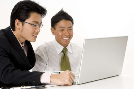 Two young men look happy with their work on a laptop (shallow depth of field) photo