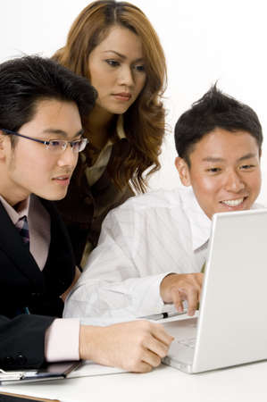 Three asian business people looking at a laptop computer Stock Photo