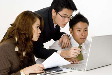 asian man face: Three young asian executives working on a project on a laptop computer