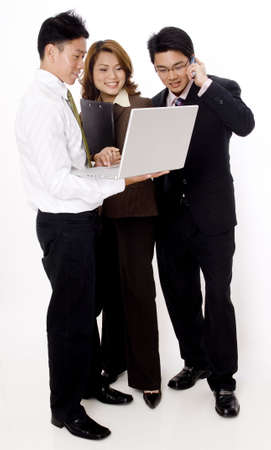 Three smiling young business people looking at a laptop computer photo