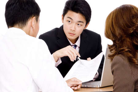 An advisor points out important parts of a document to a couple Stock Photo - 486419