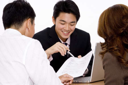 A young employee helps a couple with a form Stock Photo - 486425