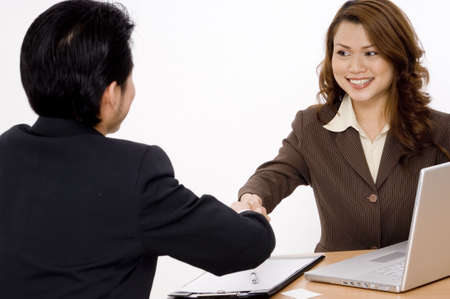 shakes hands: A smiling businesswoman shakes hands with a young businessman Stock Photo