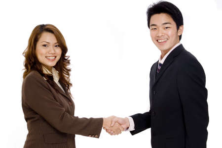 Two smiling young executives shaking hands Stock Photo