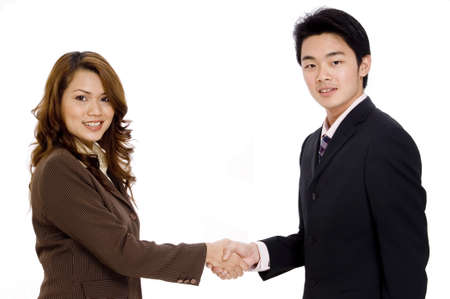shakes hands: A pretty young woman shakes hands with a young businessman