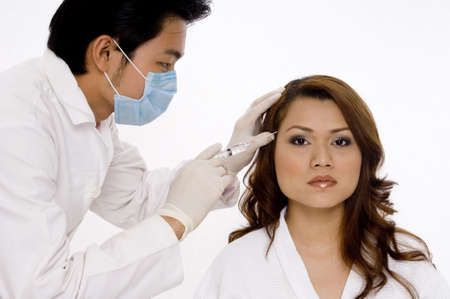 A young asian doctor administers a botox injection to a young woman (who plainly doesn't need it!) Stock Photo - 486336
