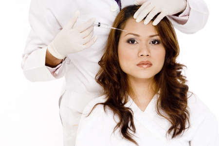 A pretty young asian woman about to have a Botox injection in her forehead