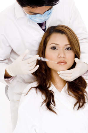 hygenic: A doctor is about to inject a young woman in the lip