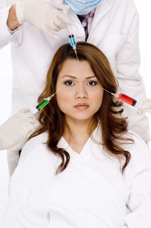 A woman with three needles about to be put into her face Stock Photo