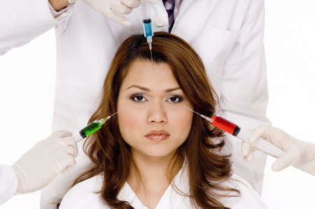 A woman faces three different coloured syringes Stock Photo - 486323