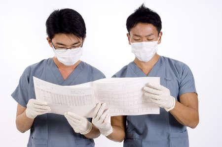 operation gown: Dos doctores j�venes examinan un listado de un electrocardiograma