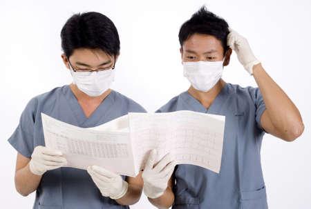 operation gown: Lucha de dos doctores que mira un listado del ecg