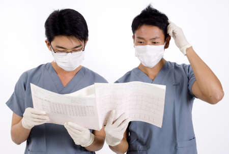 operation gown: Two doctors struggle looking at an ecg printout