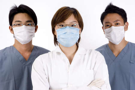 A young asian female doctor is flanked by two men in scrubs photo