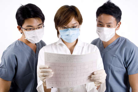 A doctor and two assistants examine the printout from an ecg machine Stock Photo