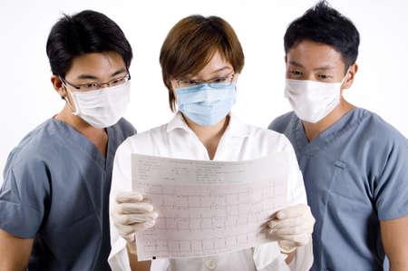 operation gown: Un m�dico y dos auxiliares de examinar la impresi�n de una m�quina ecg