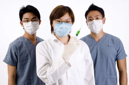 A young female doctor holds a green syringe partnered by two male doctors photo