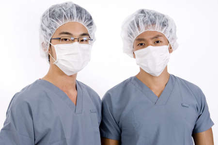operation gown: Two young asian men in medical scrubs Stock Photo