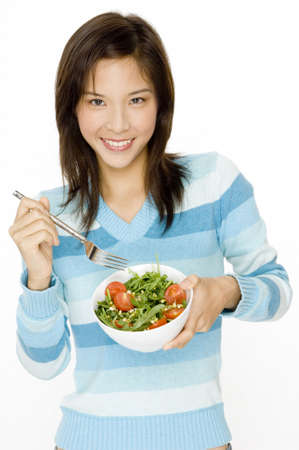 A pretty young asian woman with a small bowl of salad photo