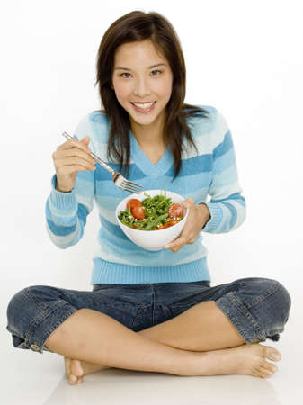 A young asian woman sitting on the floor with bowl of salad