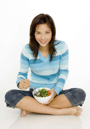 A young asian woman sitting cross-legged with a bowl of salad photo