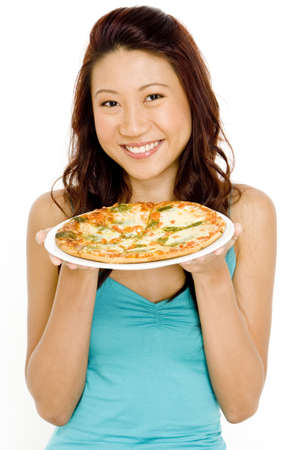 A pretty young asian woman holding a pizza and smiling