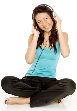 A beautiful young asian woman listens to music on headphones