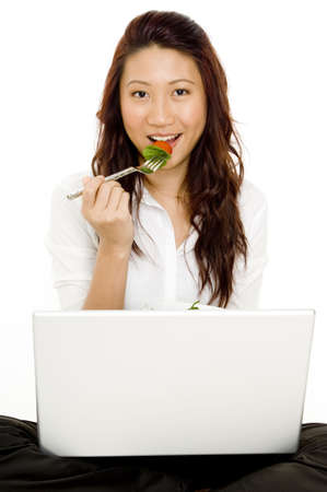 A young asian businesswoman eats lunch at her computer photo