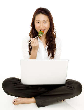 A pretty young asian woman eating salad with laptop on lap photo