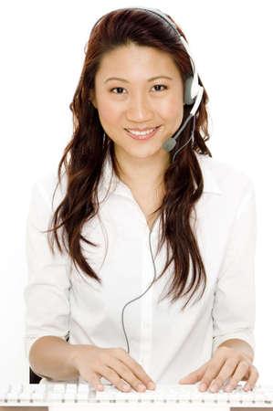 reps: Una bella asi�tica mujer con kit manos libres port�til escribiendo en un teclado