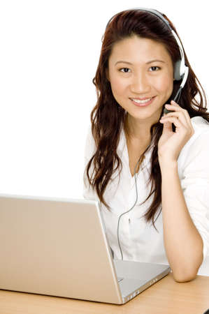 selling service: A pretty young asian woman with laptop and headset ready to help Stock Photo