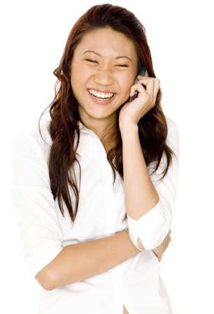 conversaciones: Una mujer asi�tica joven bonita r�e mientras que ella habla en un cellphone