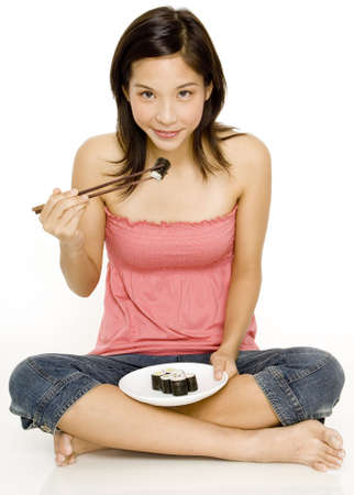 A young woman eating sushi with chopsticks sat on the floor