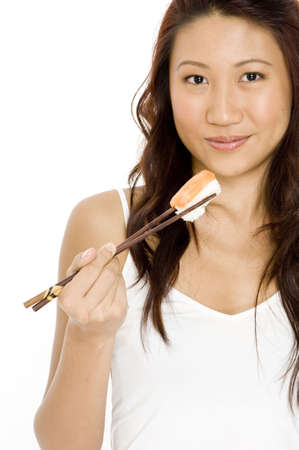 model fish: A pretty young asian woman eating salmon sushi with chopsticks Stock Photo