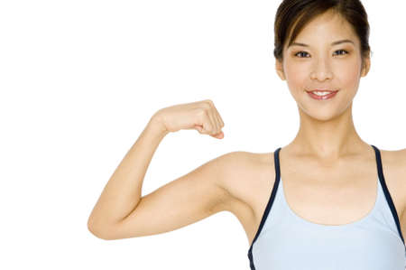 A pretty asian girl flexes one arm on white background