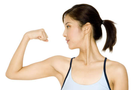 flex: A pretty young asian woman flexing her arm Stock Photo
